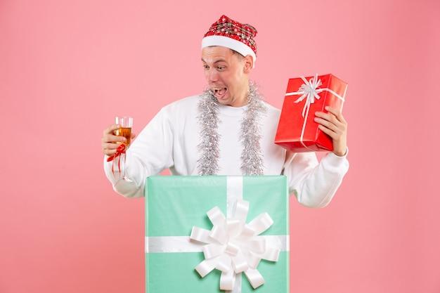 正面図ピンクの背景にプレゼントと飲み物を保持しているプレゼントの中の若い男性