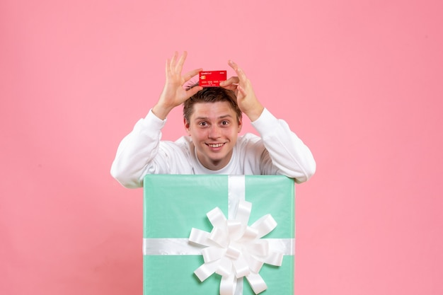 Giovane maschio di vista frontale all'interno presente che tiene la carta di credito rossa sullo scrittorio rosa
