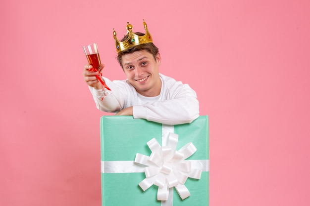 Vista frontale giovane maschio all'interno presente con corona e bicchiere di vino su sfondo rosa