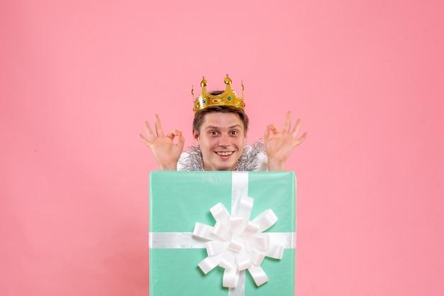 Вид спереди молодого мужчины внутри настоящего с короной на розовом полу цвета сна рождественская эмоция пижамная вечеринка