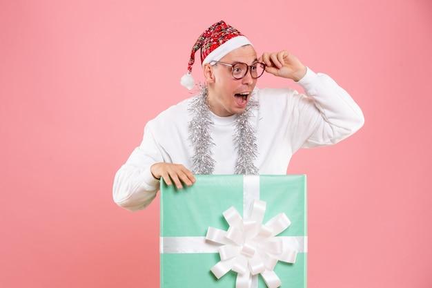 ピンクの背景を見ている花輪とプレゼントの中の正面図若い男性