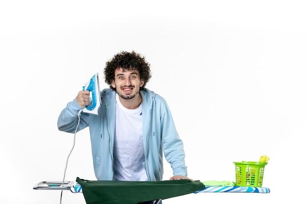 전면보기 젊은 남성 보드 뒤에서 다림질하고 흰색 배경에 웃고 집안일 다림질 세탁 감정 색상 인간의