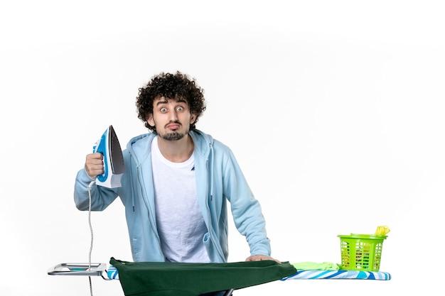 전면보기 젊은 남성 흰색 배경에 보드 뒤에서 다림질 집안일 다림질 세탁 감정 색깔 인간의