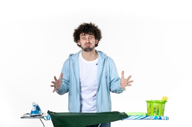 전면보기 젊은 남성 흰색 배경에 보드 뒤에서 다림질 가사 감정 색깔 인간의 철 세탁