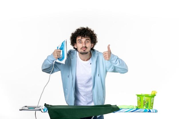 전면보기 젊은 남성 흰색 배경에 보드 뒤에 다림질 집안일 다림질 세탁 색상 인간의