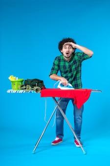 전면 보기 젊은 남성 파란색 배경 색상 집 세탁기 가사 청소에 보드에 빨간 옷을 다림질