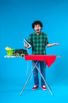 전면보기 젊은 남성 파란색 배경에 보드에 빨간 옷을 다림질 세탁기 가사 인간의 깨끗한 집