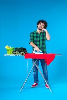 파란색 배경 색상 세탁기 가사 인간의 깨끗한 집에 보드에 빨간 옷을 다림질하는 전면보기 젊은 남성