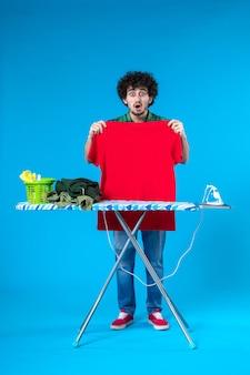 전면보기 젊은 남성 파란색 배경에 보드에 빨간 셔츠를 다림질 깨끗한 세탁기 집 색상 인간