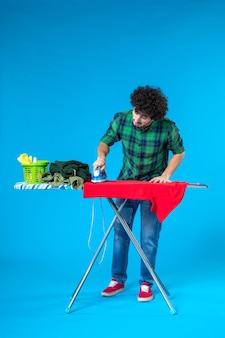 전면보기 젊은 남성 파란색 배경에 보드에 빨간 셔츠를 다림질 깨끗한 세탁기 집안일 집 색상 인간