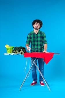 파란색 배경 인간 세탁기 가사 깨끗한 집 색상에 보드에 빨간 셔츠를 다림질하는 전면보기 젊은 남성