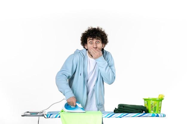 전면보기 흰색 배경에 충격을받은 얼굴로 젊은 남성 다림질 수건 철 색 남자 청소 가사 세탁 사진 옷
