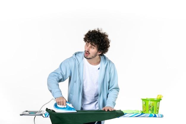 정면도 젊은 남성 흰색 바탕에 녹색 셔츠를 계속 다림질하고 있습니다. 가사 감정 색깔 인간의 철 세탁물 청소 옷