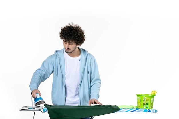 정면보기 젊은 남성 흰색 배경에 녹색 셔츠를 계속 다림질하고 있습니다. 가사 감정 색상 인간의 철 청소 옷