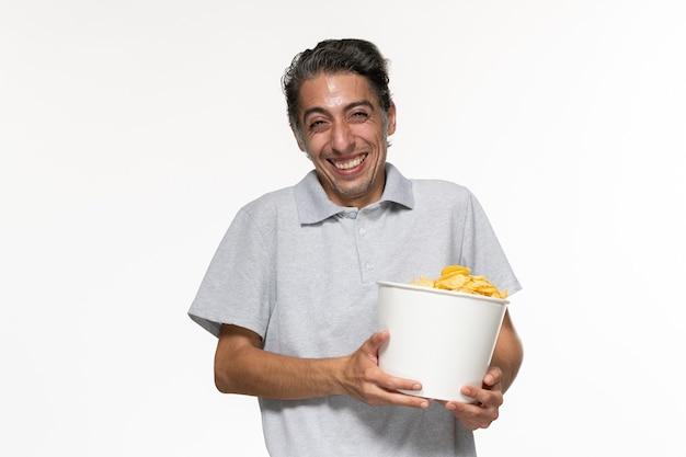 Вид спереди молодой мужчина смеется и ест картофельные чипсы на белой стене мужской удаленный кинотеатр одинокий