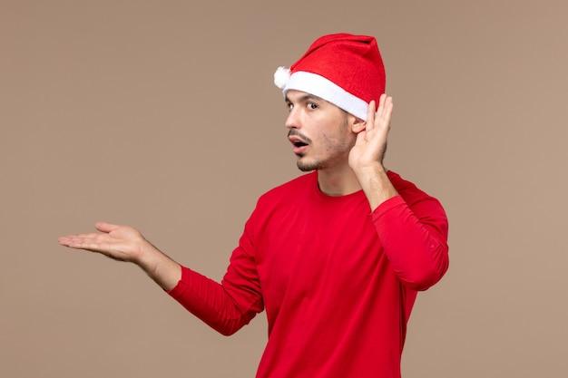 Вид спереди молодой мужчина, внимательно слушающий на коричневом фоне, рождественский праздник эмоций