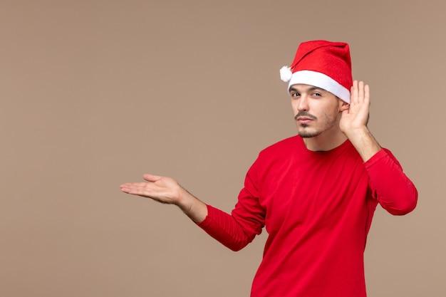 Вид спереди молодой самец, внимательно слушающий на коричневом столе, рождественский праздник эмоций