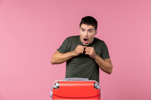 Vista frontale giovane maschio che guarda qualcosa con espressione scioccata sullo spazio rosa