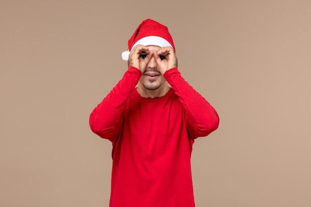 Вид спереди молодой мужчина смотрит сквозь пальцы на коричневом фоне эмоции рождественских каникул