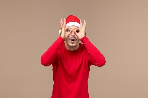 Вид спереди молодой самец, глядя сквозь пальцы на коричневый фон эмоции рождественский праздник
