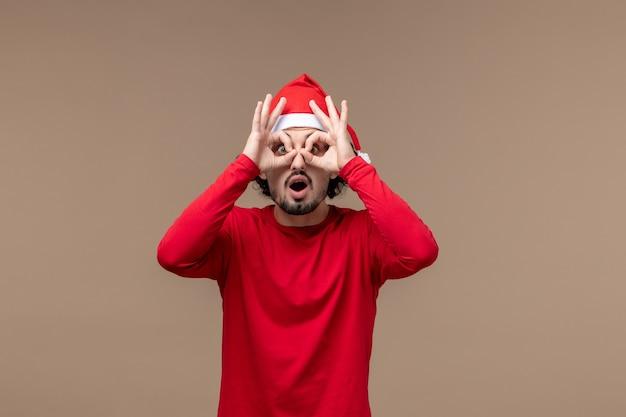 正面図茶色の背景感情クリスマス休暇で彼の指を通して見ている若い男性