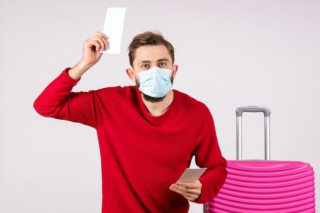 Giovane maschio di vista frontale nella maschera che tiene i biglietti aerei sul colore di vacanza del viaggio di volo del covid del virus del muro bianco