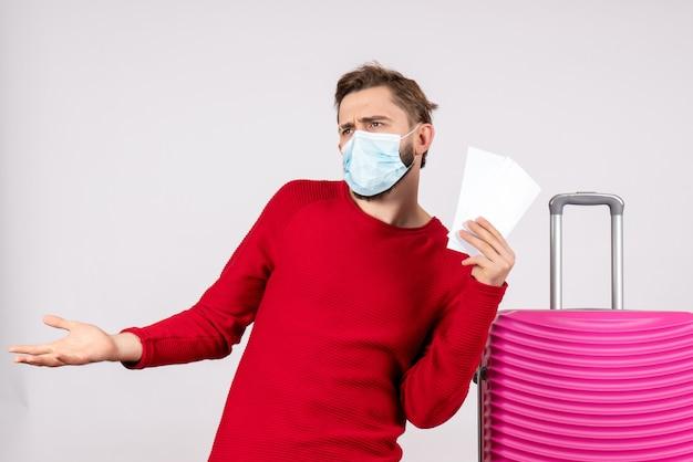 Giovane maschio di vista frontale in maschera che tiene i biglietti sul muro bianco viaggio covid- volo viaggio vacanza colore emozione