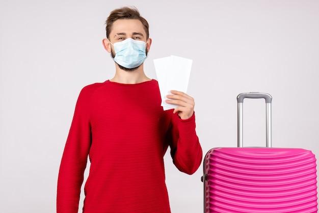 Giovane maschio di vista frontale in maschera che tiene i biglietti sul muro bianco viaggio covid- volo vacanza virus colore emozione