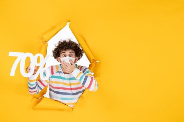 Vista frontale giovane maschio in maschera che tiene la scrittura scioccata sulla vendita gialla shopping colore covid-foto virus pandemia salute