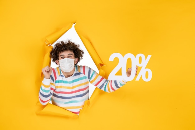 Front view young male in mask holding writing on a yellow sale coronavirus health covid- color photo pandemic