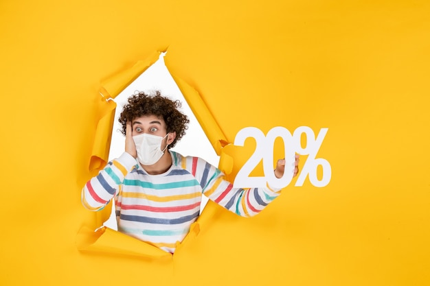 Vista frontale giovane maschio in maschera che tiene la scrittura su vendita gialla coronavirus pandemia salute foto a colori covid