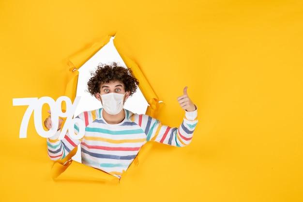 Vista frontale giovane maschio in maschera che tiene la scrittura sulla vendita gialla shopping colore covid foto virus salute pandemia