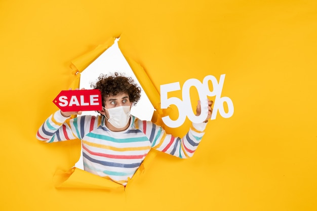 Vista frontale giovane maschio in maschera che tiene la scrittura su shopping giallo covid-foto vendita colore pandemia salute