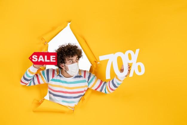 Vista frontale giovane maschio in maschera che tiene la scrittura su shopping giallo covid-foto vendita virus colore pandemia