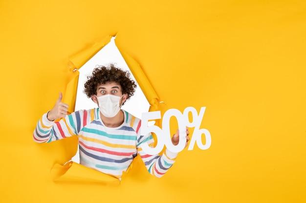 Vista frontale giovane maschio in maschera che tiene la scrittura su giallo shopping salute covid-virus foto vendita colore