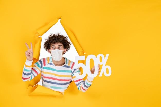 Vista frontale giovane maschio in maschera che tiene la scrittura su shopping giallo pandemia covid-virus foto vendita colore