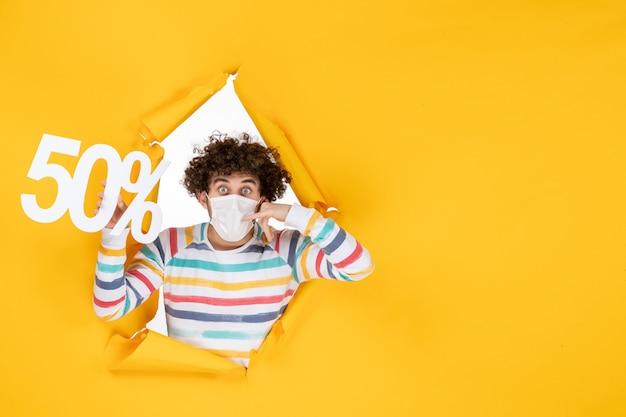Vista frontale giovane maschio in maschera che tiene la scrittura sul virus giallo shopping covid-foto vendita colore pandemia salute