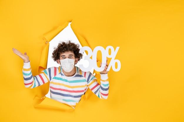 Vista frontale giovane maschio in maschera che tiene su colore giallo shopping salute covid-foto pandemia