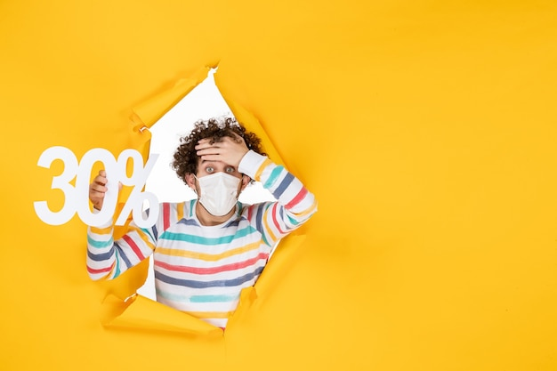 Front view young male in mask holding on yellow color shopping health covid- photo virus