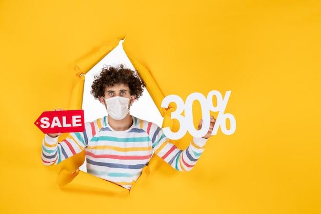 Vista frontale giovane maschio in maschera che tiene il colore giallo pandemico shopping rosso salute foto virus vendita