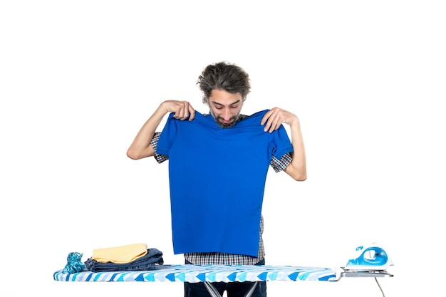 정면도 젊은 남성 흰색 바탕에 파란색 셔츠를 측정하고 있습니다.