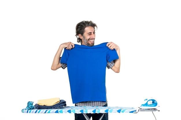 정면도 젊은 남성 흰색 바탕에 파란색 셔츠를 측정하고 있습니다. 집안일 일 아이언 맨 옷 깨끗한 기계 세탁
