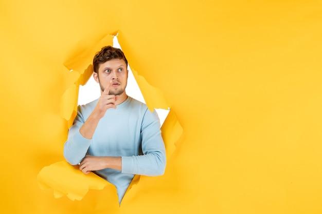 Вид спереди молодой самец на желтом разорванном фоне
