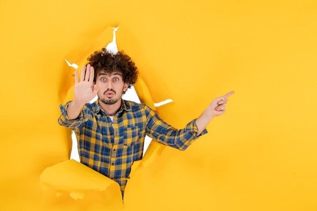 黄色の破れた背景の正面図若い男性
