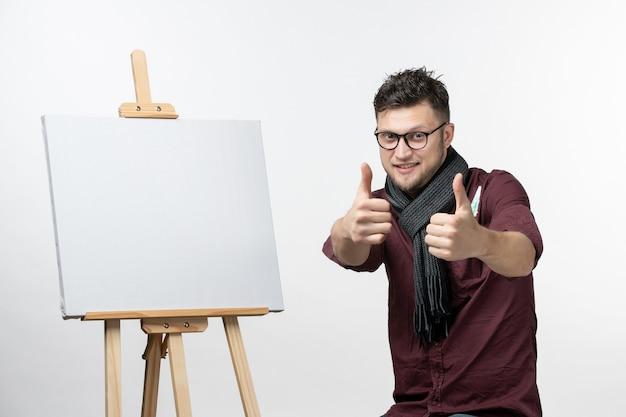 白い背景の上のイーゼルと一緒に正面図若い男性画家