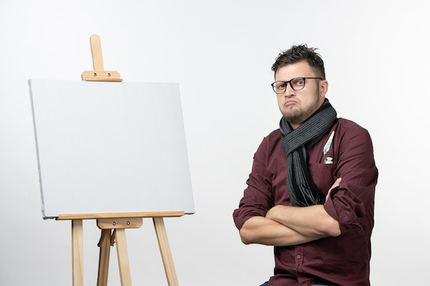 Front view young male painter along with easel on a white background