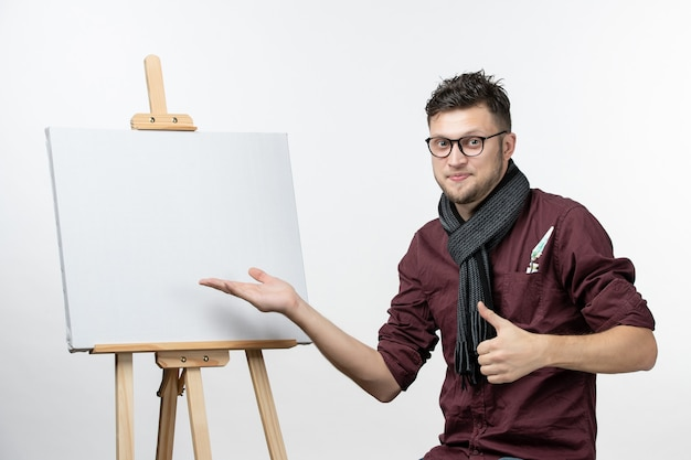Front view young male painter along with easel on white background