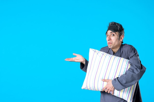 Front view young male in pajamas holding pillow on blue background bedroom insomnia nightmare dream dark night bed sleep