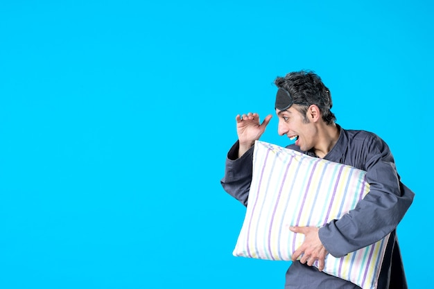 Front view young male in pajamas holding pillow on blue background bedroom insomnia nightmare dream dark night sleep rest
