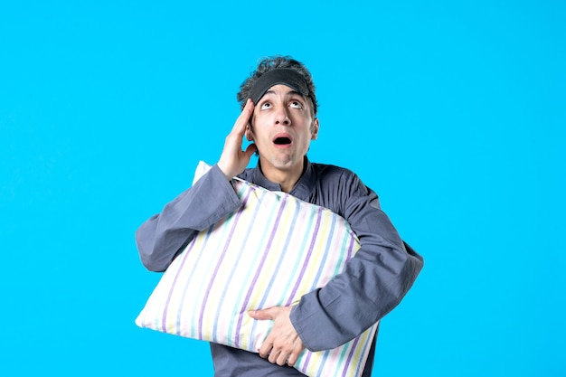 Front view young male in pajamas holding pillow on blue background bedroom rest insomnia sleep bed nightmare dreams dark night